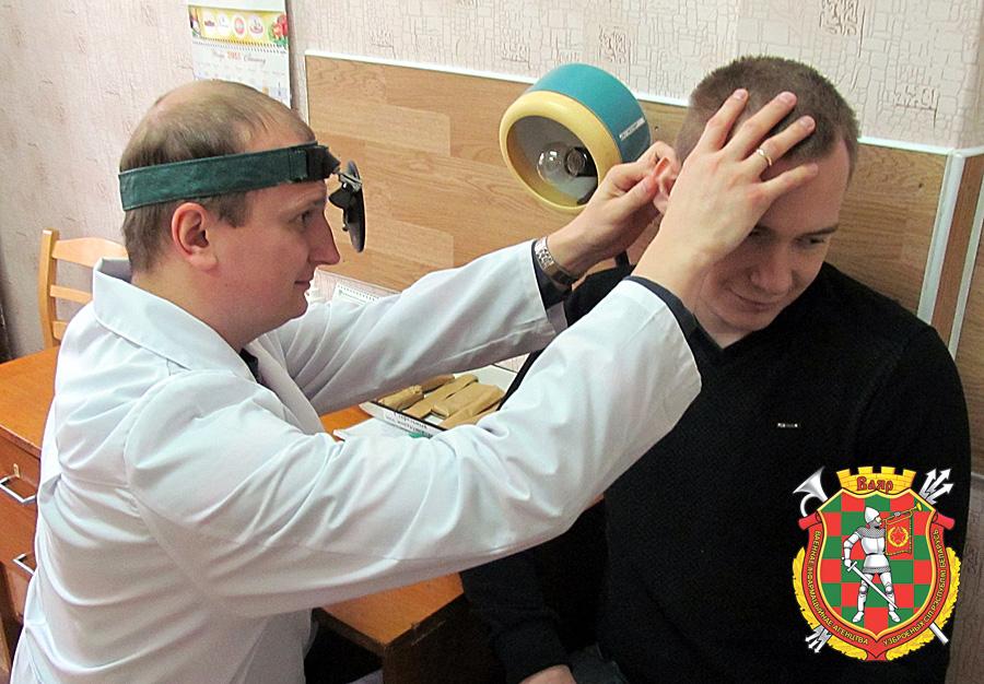 Врач-оториноларинголог Олег Лысковец проводит контрольный медицинский осмотр призывника Сергея Кудрявцева
