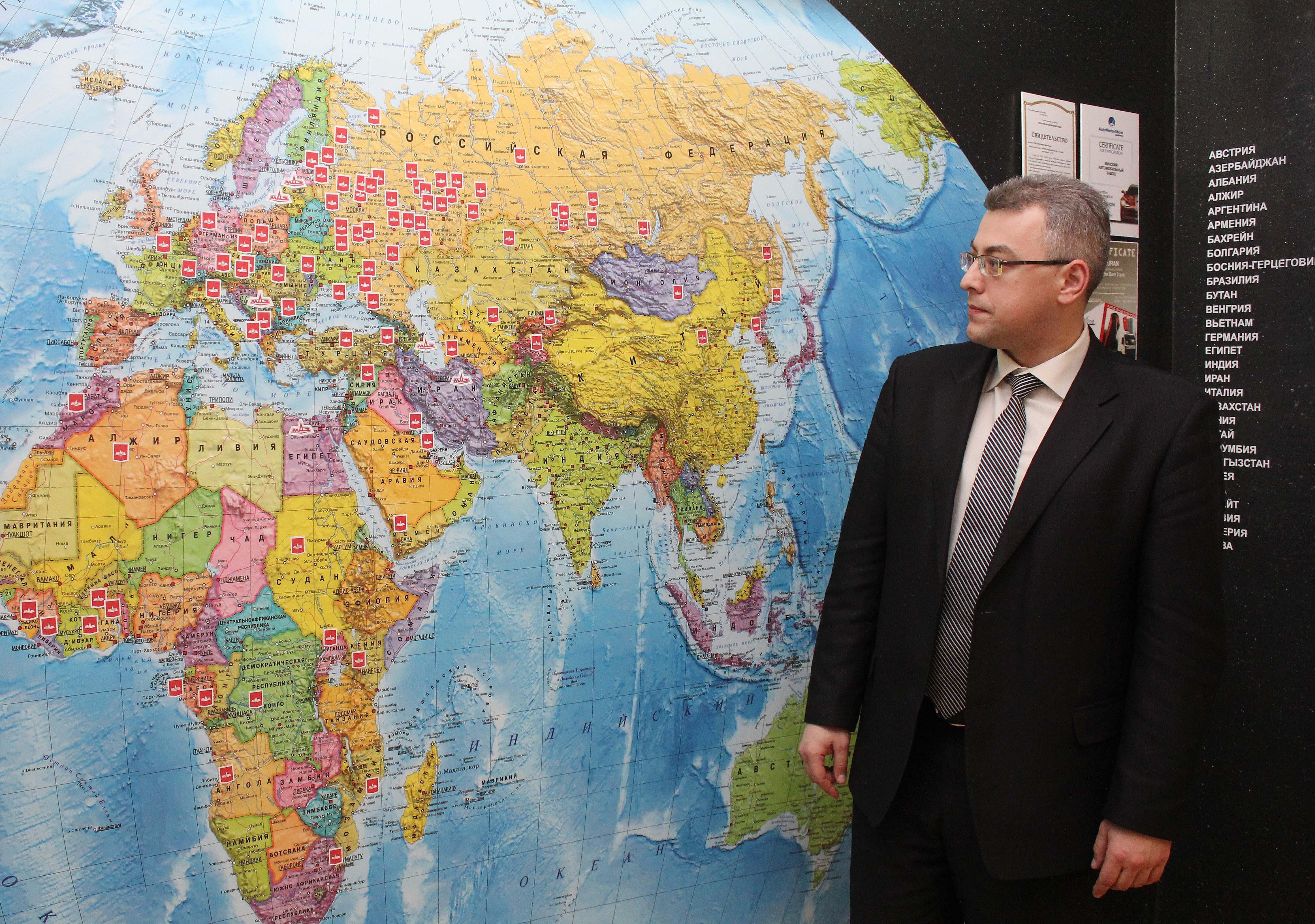 Евгений Крупенько у карты мира, на которой продемонстрирована география МАЗа